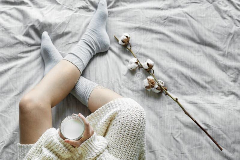 Weiße Frau, die auf Bett mit heißer Milch im Winter sitzt lizenzfreies stockfoto