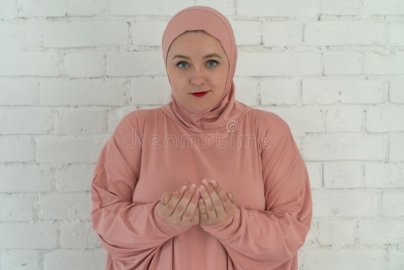Weiße Frau mit blauen Augen in einem rosa hijab betet auf einem weißen Hintergrund Religi?ses Lebensstilkonzept der Leute stockfotografie