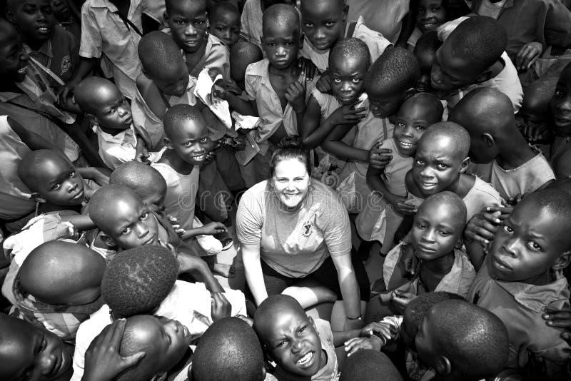 Weiße Frau umgeben von den afrikanischen Kindern stockbilder