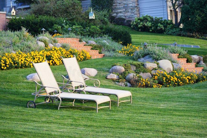 Weiße Gartenstühle gestalteten Yard landschaftlich stockfotografie