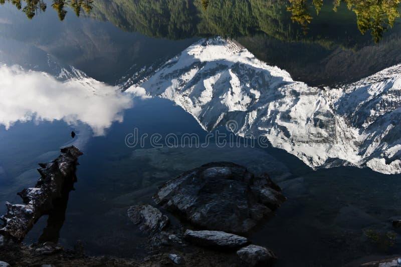Weiße Gebirgskante reflektierte sich in einem See stockfotografie