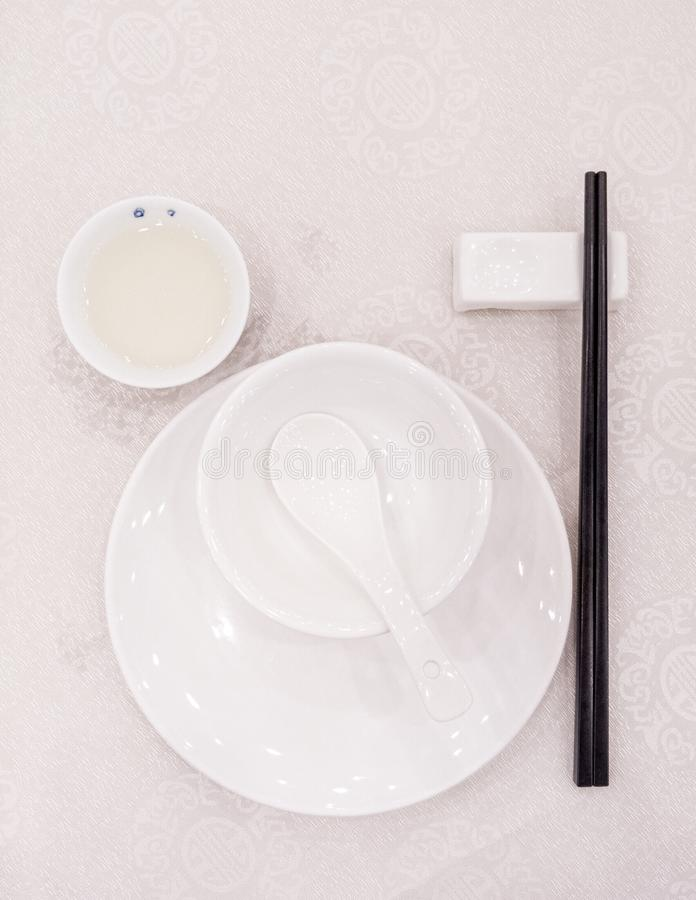 Weiße Gerichte in einem chinesischen Restaurant mit schwarzen Stäbchen lizenzfreies stockfoto