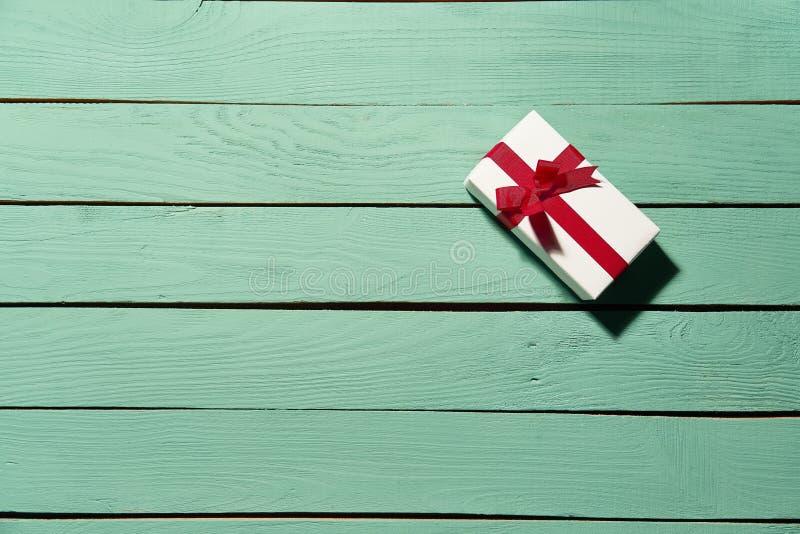 Weiße Geschenkbox mit rotem Bogen auf grünen hölzernen Planken stockfotos