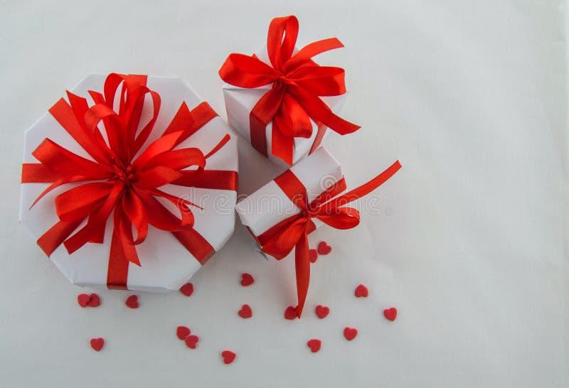 Weiße Geschenkboxen, verschiedene Formen mit roten dekorativen Bändern lizenzfreie stockfotos