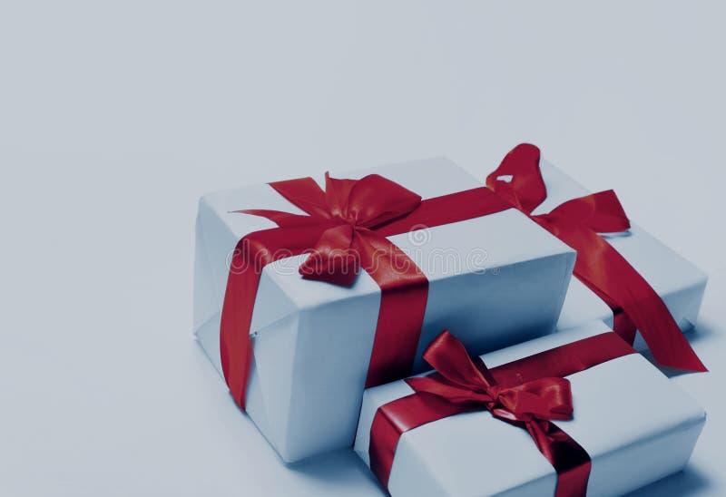 Weiße Geschenke mit rotem Band beugen, lokalisiert auf Weiß stockbilder