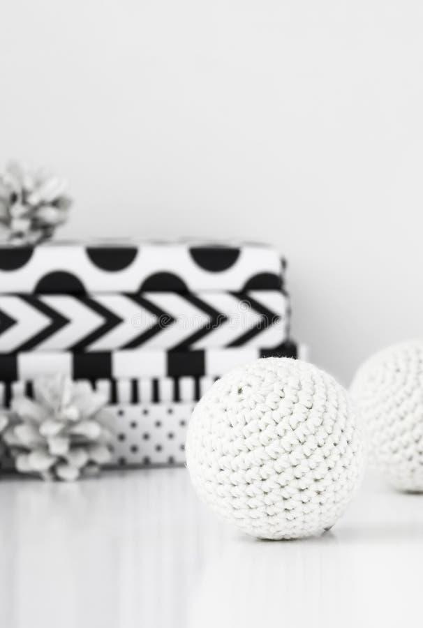 Weiße Häkelarbeit Weihnachtsbälle mit modernen Geschenken und Kiefernkegeln stockfotografie