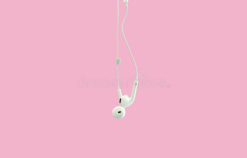Weiße hängende In-Ohr-Kopfhörer-Kopfhörer lokalisiert auf einem rosa Hintergrund stockbild