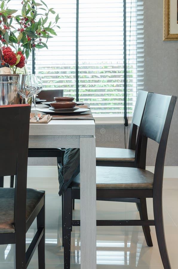Weiße hölzerne dinning Tabelle mit dunklen Holzstühlen stockfotografie