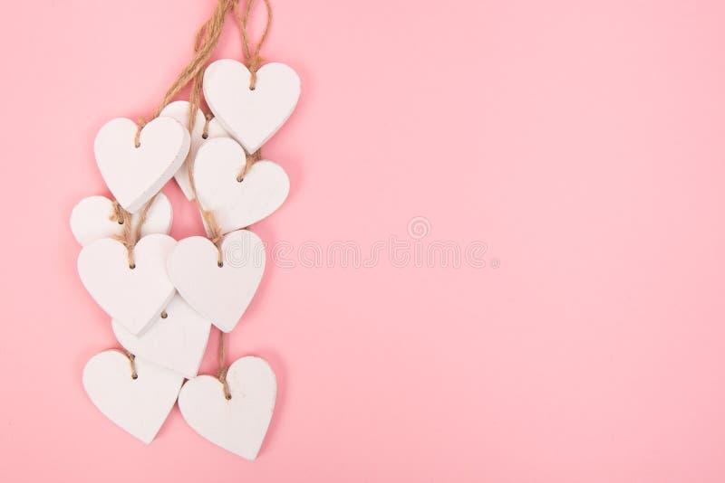 Weiße hölzerne Herzen auf einem rosa Hintergrund stockbilder