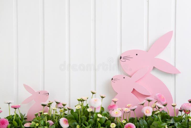 Weiße hölzerne Ostern-Dekoration mit Blumen und ein rosa Häschen für stockfotografie