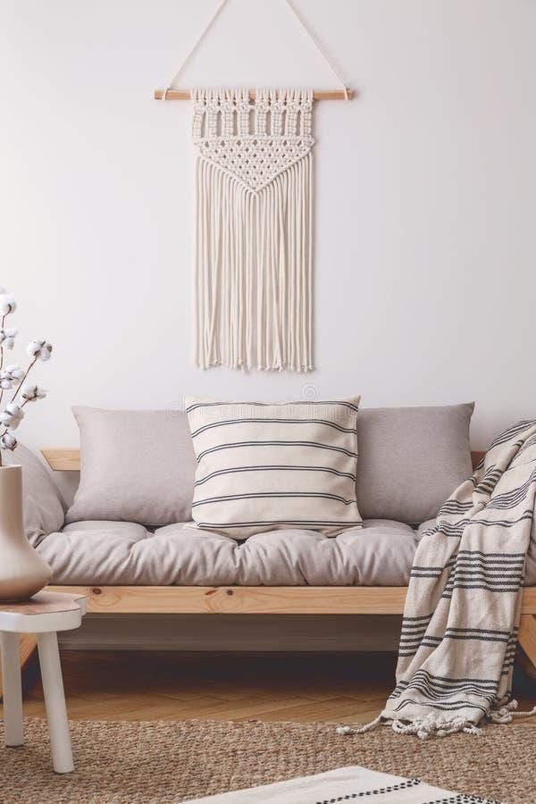 Weiße handgemachte Makramee über bequemem beige Wohnzimmersofa mit Los von Kissen und von Decke mit Streifen lizenzfreie stockfotografie