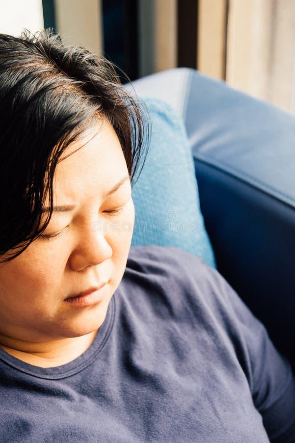 Weiße Haut Asien-Frauen 40s, die auf Sofa denkt stockfotos
