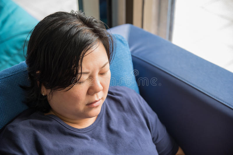 Weiße Haut Asien-Frauen 40s, die auf Sofa denkt lizenzfreies stockfoto