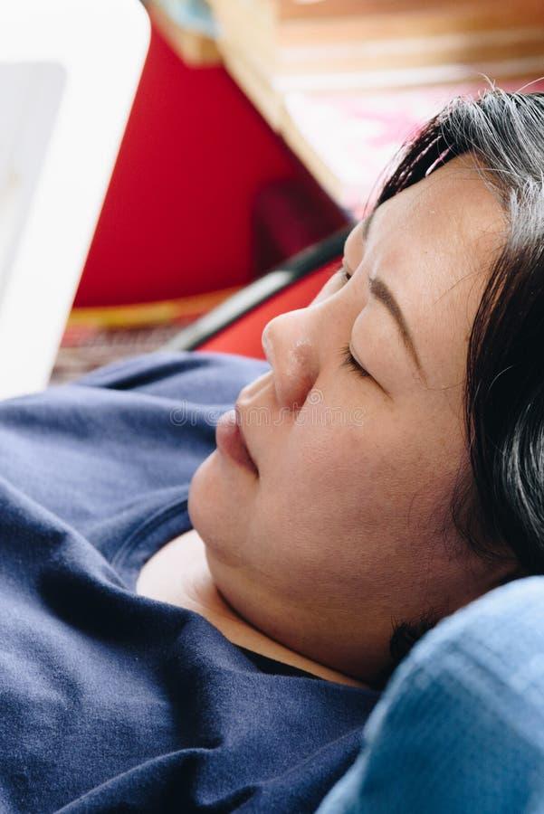 Weiße Haut der Asiatinnen 40s, die auf Sofa denkt stockbild