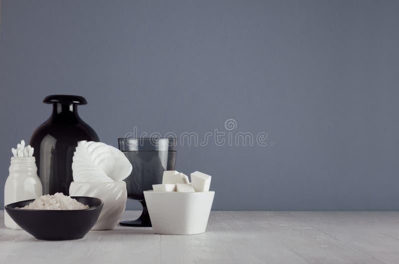 Weiße Hautpflegeprodukte und Zubehör auf weißem hölzernem Regal und dunkelgrauer Wand, eleganter Badezimmerdekor stockfotos
