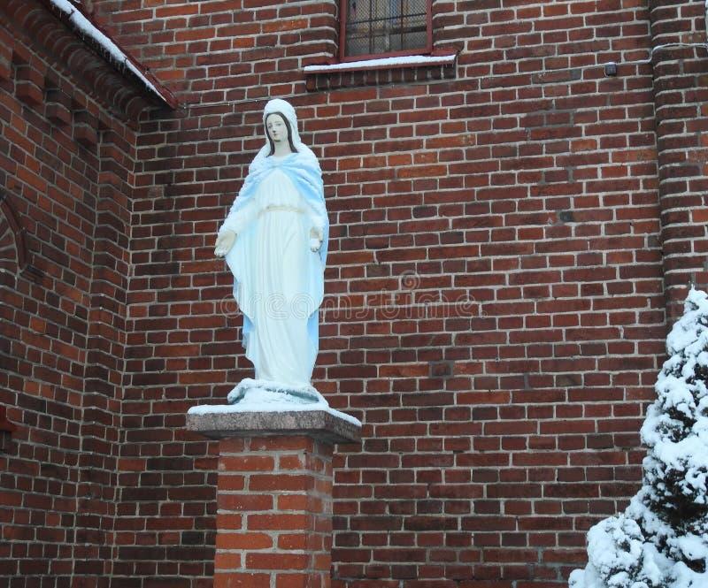 Weiße heilige Mary nahe roter Kirche, Litauen stockfotografie