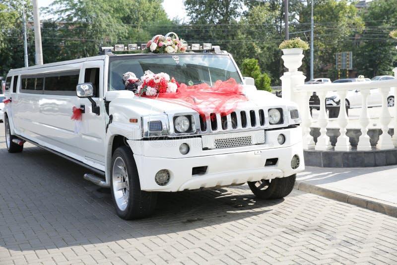 Weiße Heiratslimousine verziert mit roten Bändern, Eheringen und Blumen Ist hier ein Foto von 4 Strahlenk?mpfern in der Anordnung lizenzfreies stockfoto
