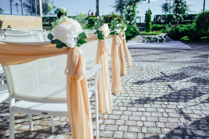 Weiße Heiratsstühle mit Blumen auf weddind lizenzfreie stockbilder