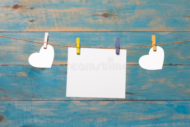 Weiße Herzen, die über blauem hölzernem Hintergrund mit leerem pape hängen lizenzfreie stockfotos