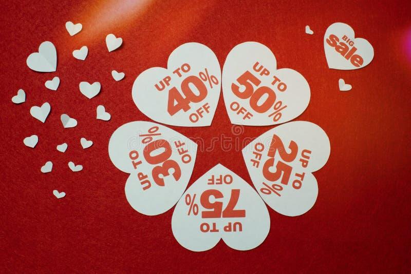Weiße Herzen formten Verkaufsförderungsumbau gegen einen roten Hintergrund stockbilder