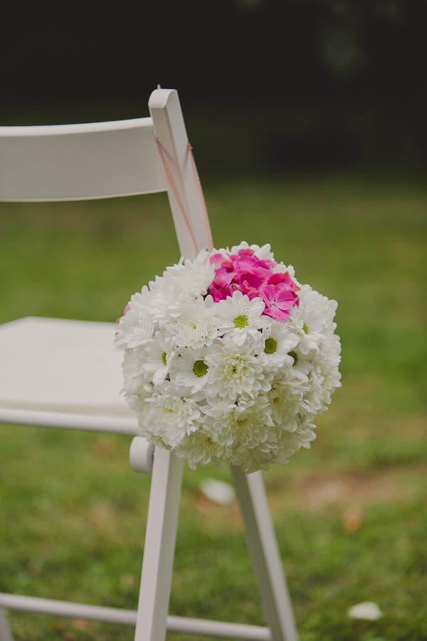 Weiße Hochzeitsstühle mit schöner Blume stockfotografie