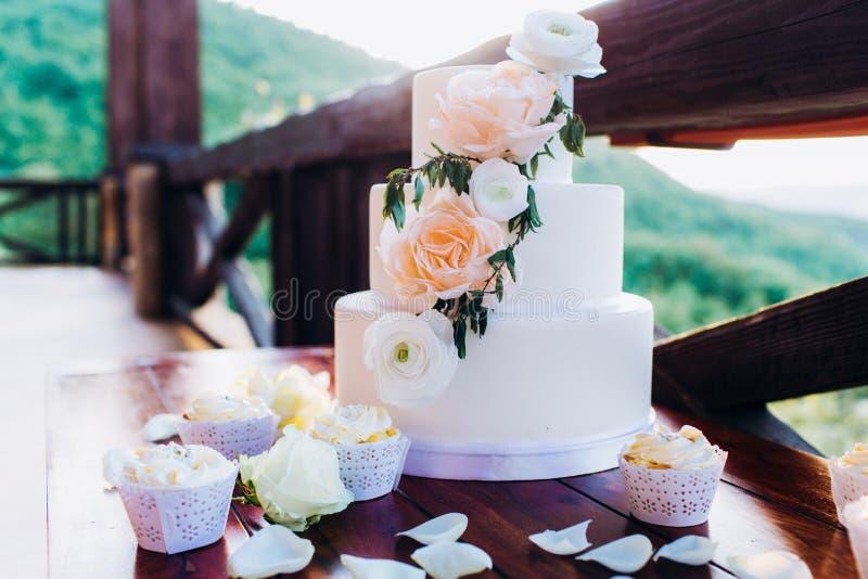Weiße Hochzeitstorte mit Blumen auf einem Holztisch lizenzfreies stockfoto