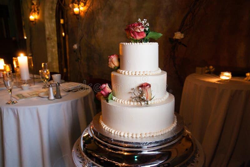 Weiße Hochzeitstorte mit roten Rosen auf einer silbernen Servierplatte mit einer Hochzeitstafel und Kerzen im Hintergrund stockfoto