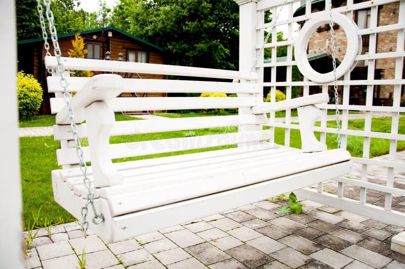 Weiße Holzbank wie ein Schwingen Im Park an einem Sommernachmittag stockfotos