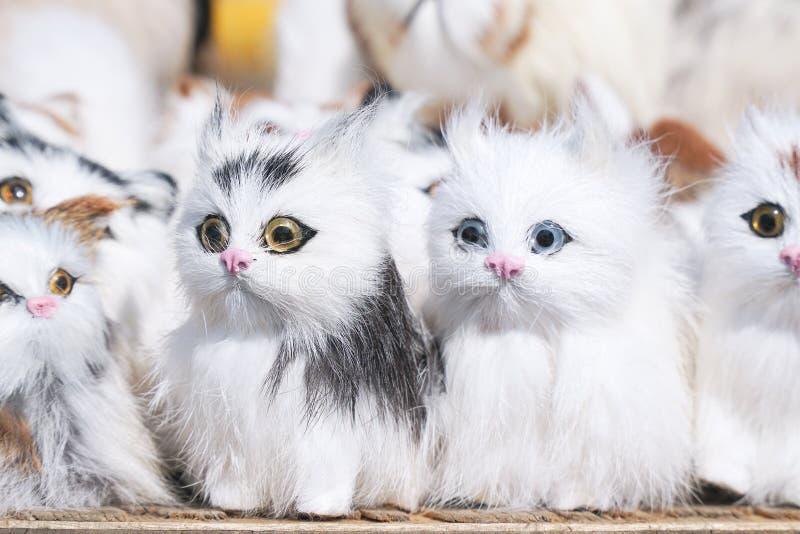 Weiße Kätzchen der weichen Spielwaren, die vor Kamera sitzen stockbilder