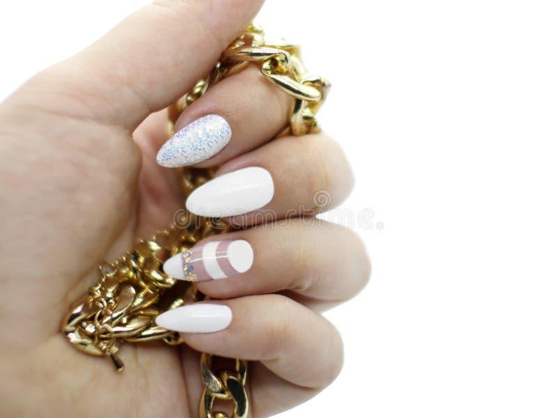 Weiße künstlerische Nagelkunst auf langen Nägeln mit goldenem Schmuck mit weißem Hintergrund stockbild