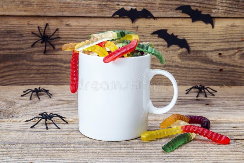 Weiße Kaffeetasse Halloweens mit gummi Würmern und Spinnen auf dem w stockfotografie