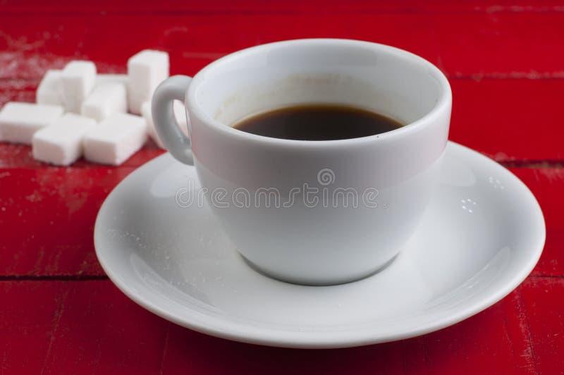 Wei?e Kaffeetasse mit den Zuckerw?rfeln lokalisiert auf einem roten Hintergrund stockfotografie
