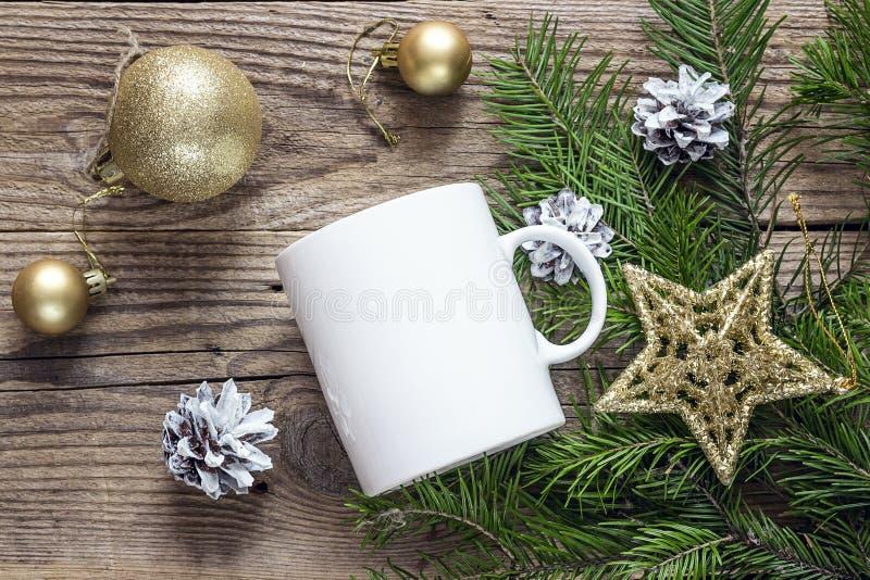 Weiße Kaffeetasse mit Goldweihnachtsdekorationen und Tanne branche stockfoto