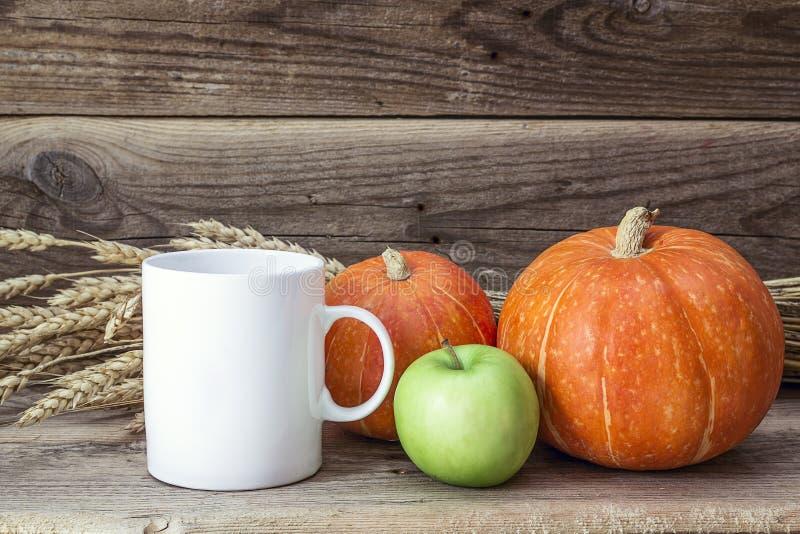 Weiße Kaffeetasse mit Kürbisen, grünem Apfel und den Ohren von Weizen O lizenzfreie stockfotos