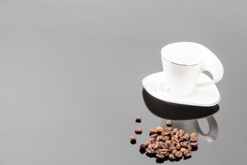 Weiße Kaffeetasse mit Kaffeebohnen auf dem grauen Spiegelhintergrund Kopieren Sie Platz stockfoto
