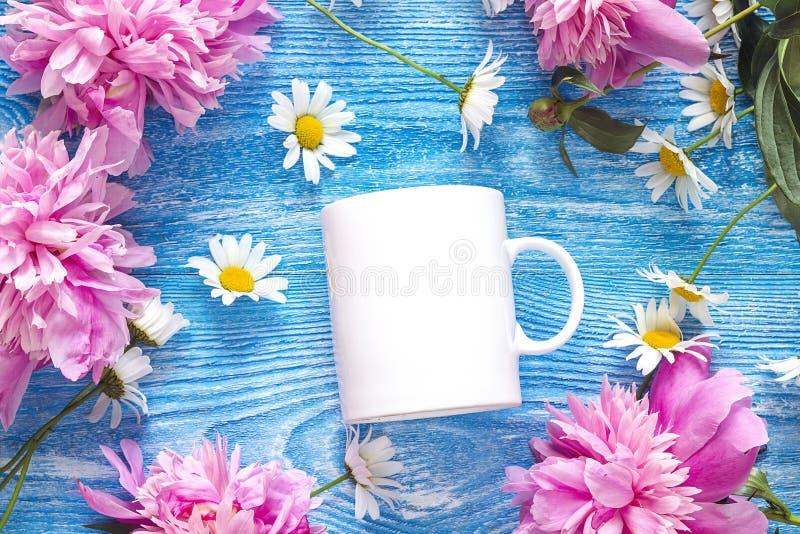 Weiße Kaffeetasse mit Kamillenblumen und rosa Pfingstrosen auf Blau stockfotografie