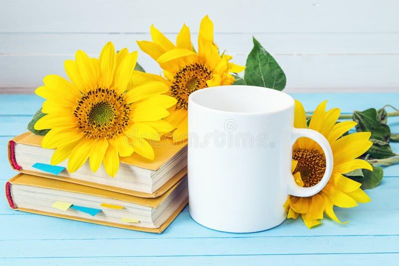 Weiße Kaffeetasse mit Sonnenblumen und gelben Büchern auf blauem hölzernem stockbilder