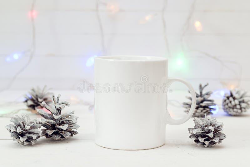 Weiße Kaffeetasse mit Weihnachtskegeln und brennender Girlande platz lizenzfreies stockfoto