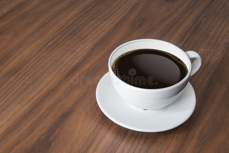 Weiße Kaffeetasse und heißer Espressokaffee auf Holztisch stockbild
