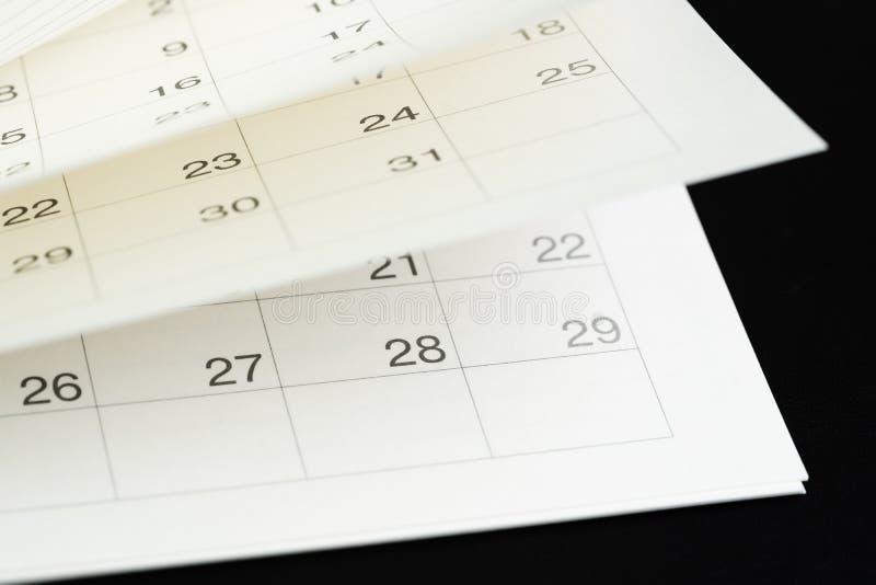 Weiße Kalenderumblätterseiten mit dunkelschwarzem Hintergrund, die als Zeitfliege, Saisonpass oder Erinnerung verwendet werden un lizenzfreies stockbild