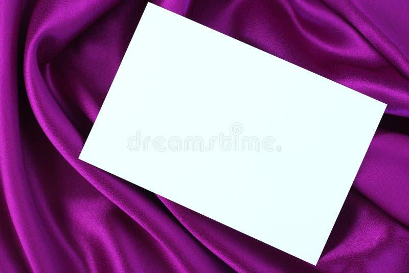 Weiße Karte auf purpurrotem Satin stockbild