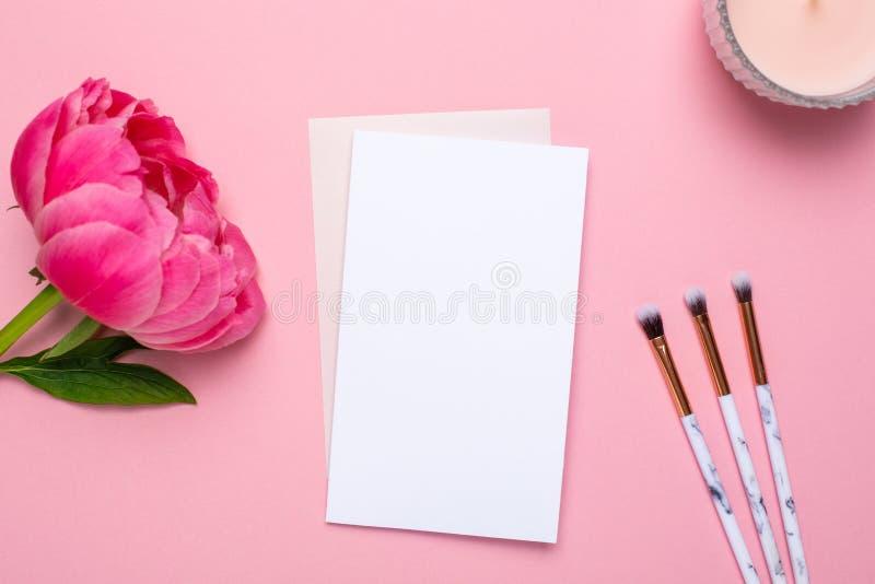 Weiße Karte mit Make-upbürsten und schöne Blumenpfingstrose auf einem rosa Hintergrund Muttertag und Feiertage stockfotos