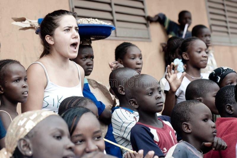 Weiße kaukasische junge Frau spielt mit Schwarzafrikanerleuten in einem ländlichen Dorf stockbild