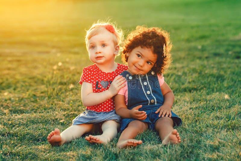 Weiße kaukasische und lateinische hispanische Babys, die draußen im Park umarmen stockbilder