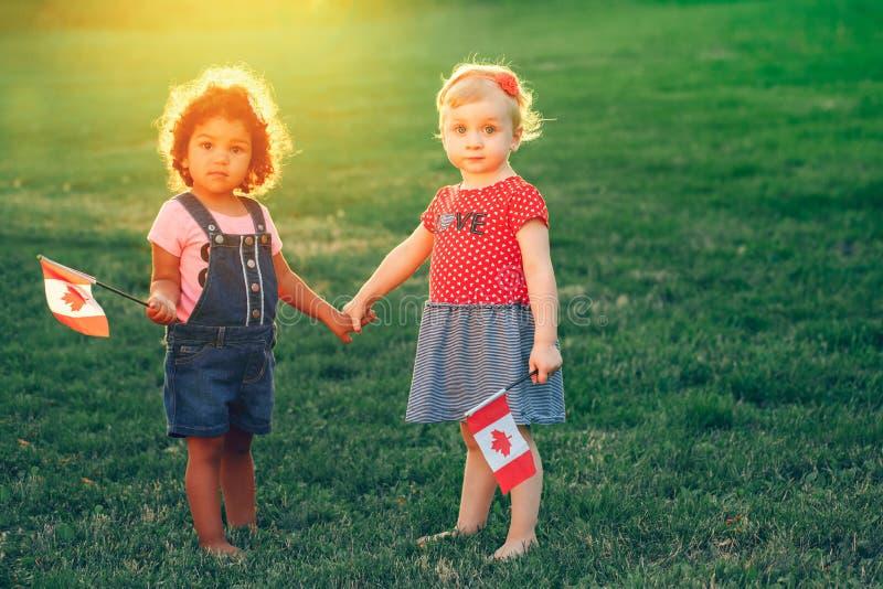 Weiße kaukasische und lateinische hispanische Babys, die draußen im Park umarmen lizenzfreie stockfotos