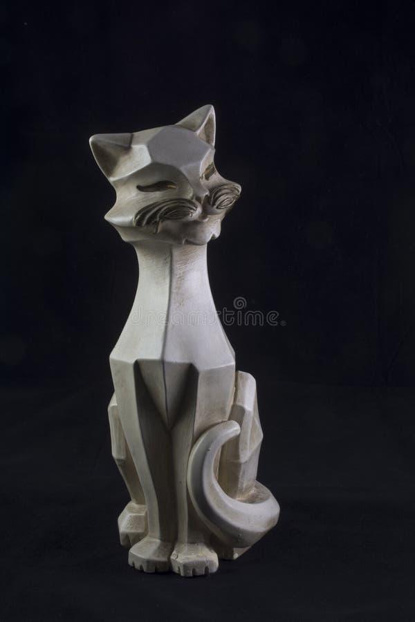 Weiße keramische Katze auf Schwarzem lizenzfreie stockfotografie