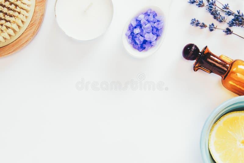 Weiße Kerze, Blumen des Lavendels, dekorative Flaschen, Bürste für Massage, Seesalze, Zitrone auf dem weißen Hintergrund Entspann lizenzfreie stockfotos
