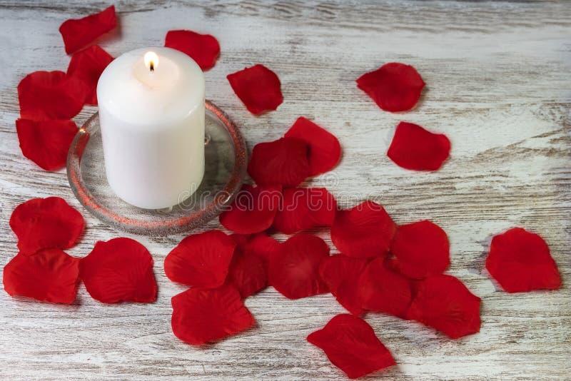 Weiße Kerze, die auf rustikalem Hintergrund brennt stockbild