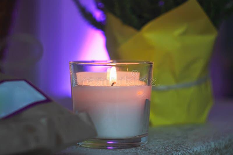 weiße Kerze in einem Glas auf einer Tabelle stockfoto