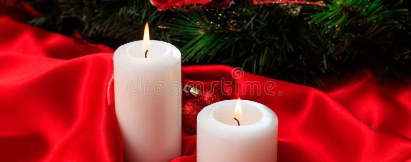 Weiße Kerzen auf dem roten Satin, der auf einem dunklen Hintergrund, Fahne brennt stockfotografie